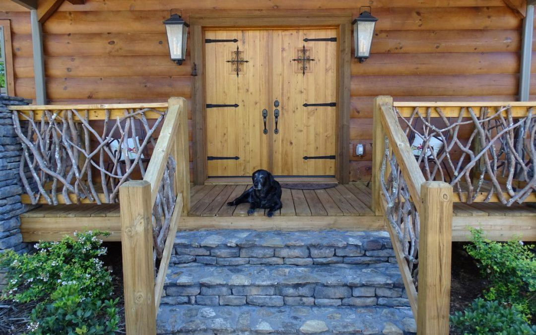 Exterior photo of front door with rustic porch railing